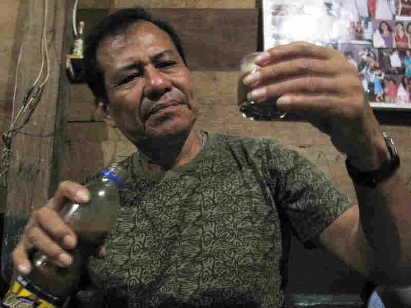Juan Tangoa, a shaman and medicine man, looks at the glass of ayahuasca