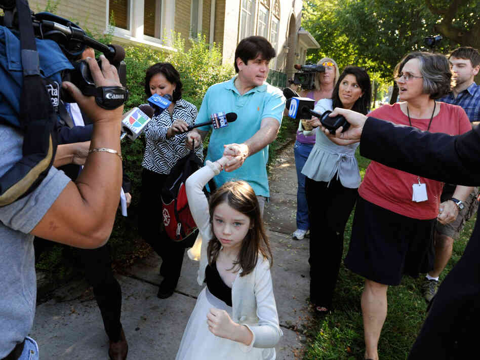 Former Illinois Gov. Rod Blagojevich talks with reporters Wednesday as he leaves his home.