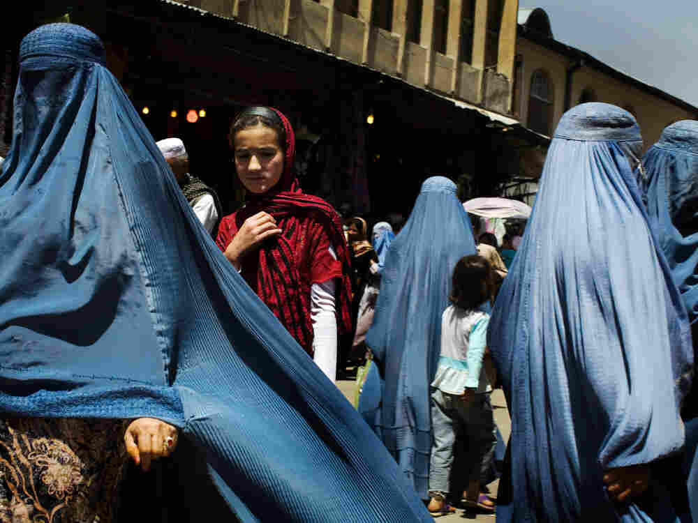 Women walk at a street market in downtown Kabul