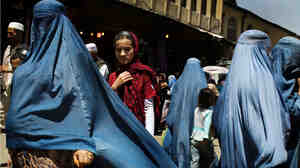 Women walk at a street market in downtown Kabul