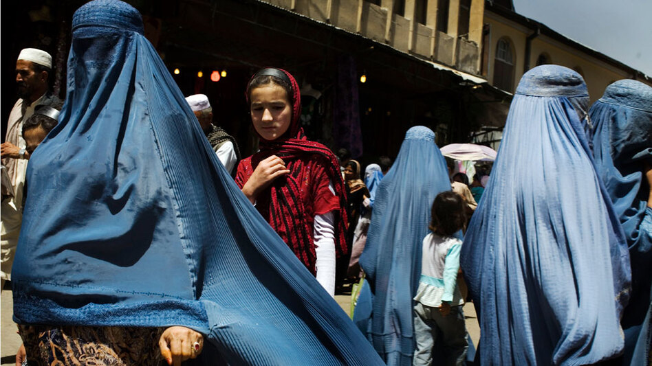 Women walk at an outdoor market in downtown Kabul. The resurgent Taliban and several recent executions in accordance with an extreme interpretation of Shariah law have human-rights activists worried, particularly for women.
