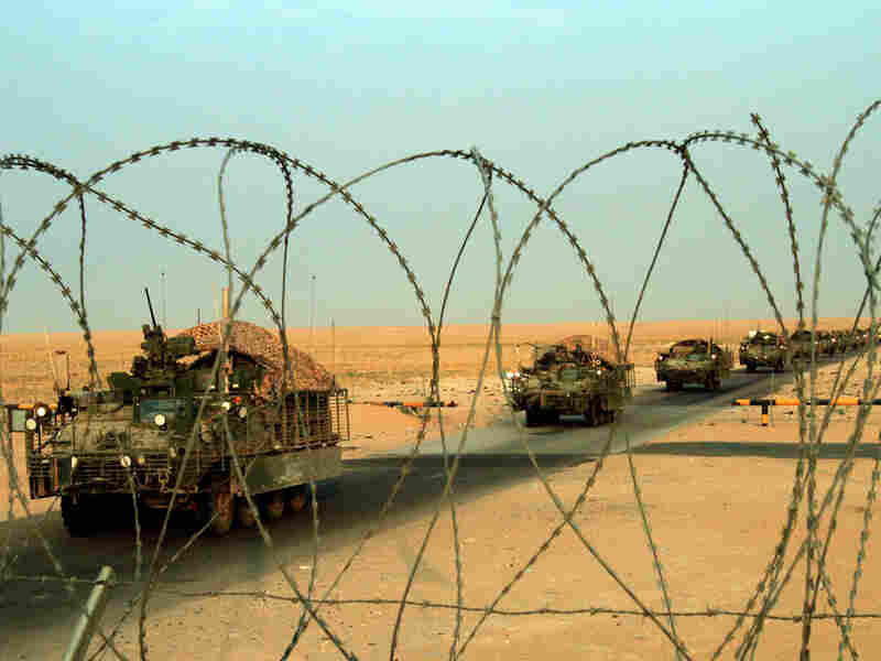 A column of Stryker armored vehicles carrying Army troops crosses the border from Iraq into Kuwait.