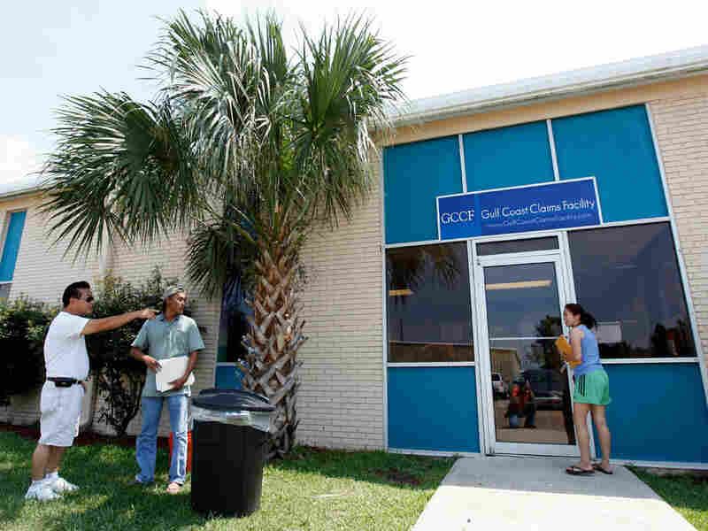 Local residents stand outside the new Gulf Coast Claims Facility in New Orleans