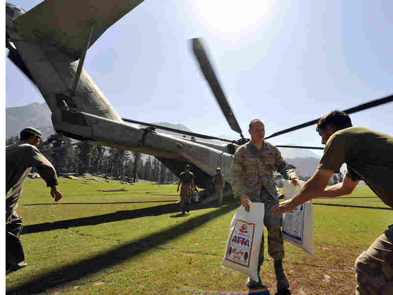 Soldiers unload relief supplies from helicopter