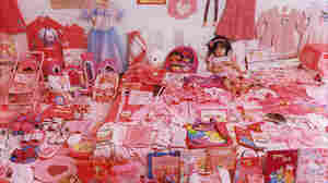 A little girl sits in a room of pink things