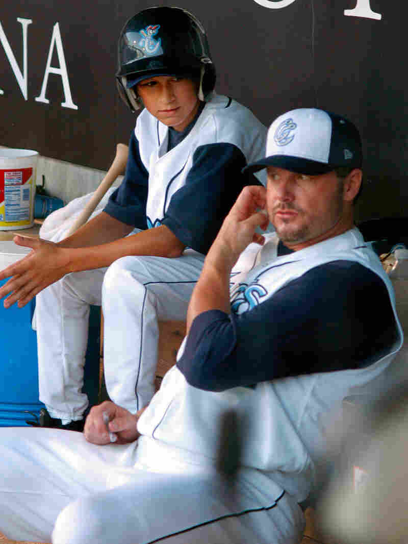 A batboy watches pitcher Roger Clemens in the dugout during a Corpus Christi Hooks baseball game.