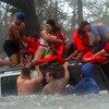 Volunteers rescue a family following Hurricane Katrina.