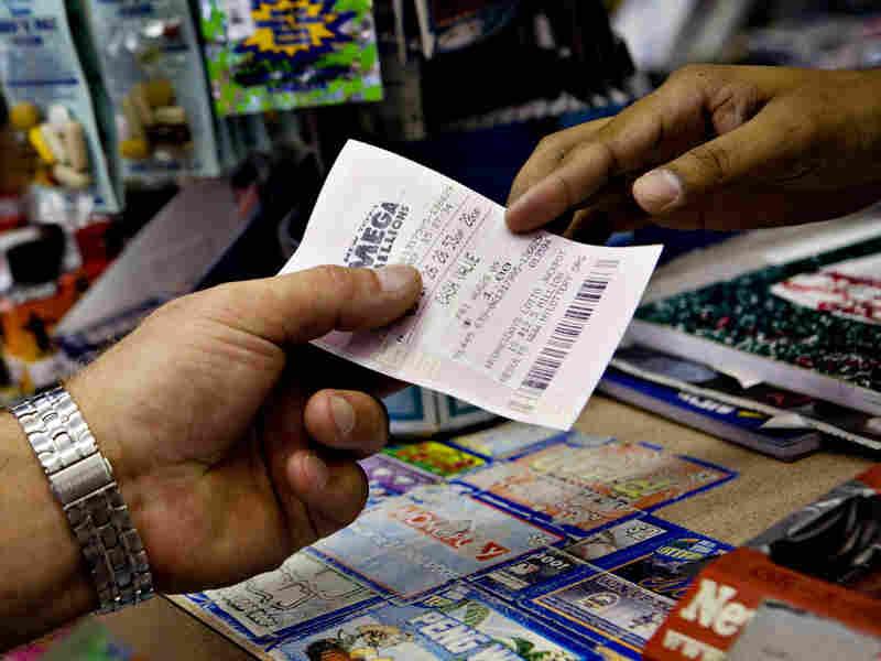 A salesman hands a customer a Mega Millions ticket in a New York deli last August.