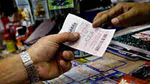 A salesman hands a customer a Mega Millions ticket in a New York deli last August.