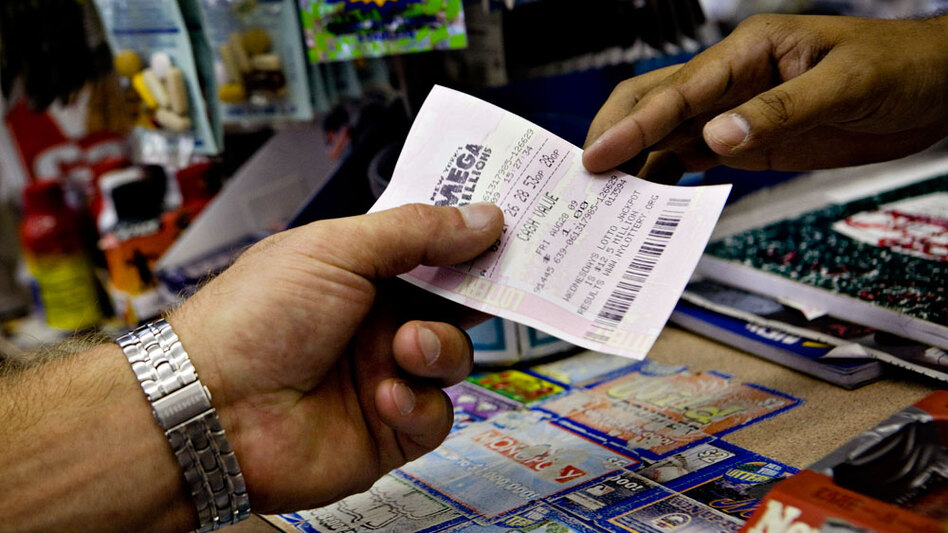 A salesman hands a customer a Mega Millions ticket in a New York deli last August. Despite the recession, national lottery sales were up $1 billion over the past year.