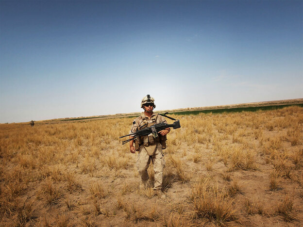 """U.S. Marine Lance Cpl. Josh Yang marches through rural scrubland near Khan Neshin in Helmand Province, Afghanistan, in March. Defense Secretary Robert Gates says the Marine Corps has gotten away from its """"maritime soul"""" while working in the desert."""