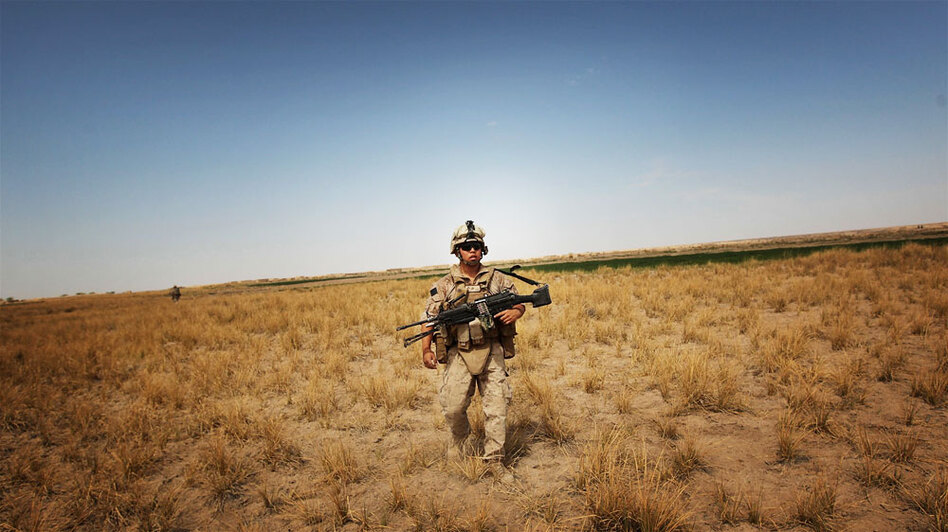"U.S. Marine Lance Cpl. Josh Yang marches through rural scrubland near Khan Neshin in Helmand Province, Afghanistan, in March. Defense Secretary Robert Gates says the Marine Corps has gotten away from its ""maritime soul"" while working in the desert."
