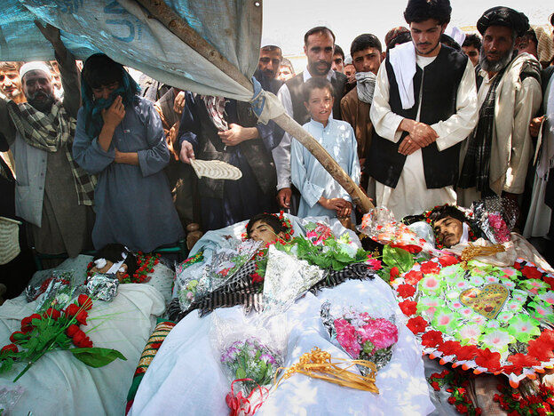 Villagers stand around the bodies of three brothers who were killed by American forces during the raid. The U.S. says they called for the men to come out peacefully and only fired when they saw an AK-47 rifle. The family gives a starkly different account of what happened.