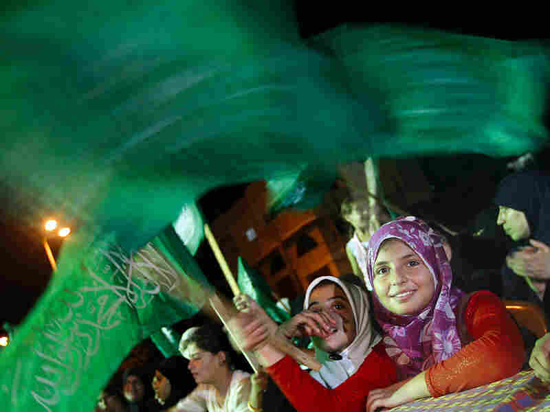 Palestinian women wave Hamas flag during a rally in Gaza City