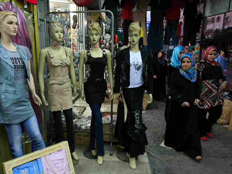 Palestinian women walk past shops in Gaza City