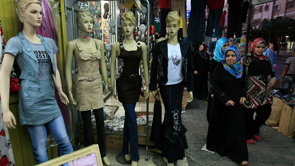 "Palestinian women walk past mannequins outside shops in Gaza City in July after Hamas announced new regulations on shops selling women's clothes as part of a campaign to safeguard ""public morality."" Some see the new rules as a move by Hamas to strengthen its Islamist credentials."