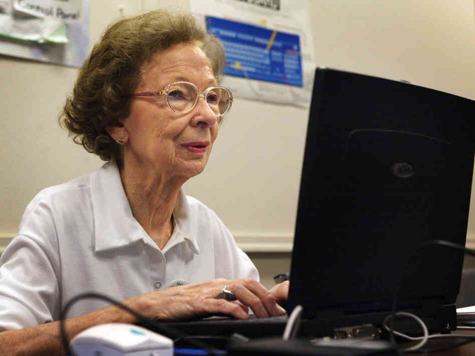 77-year-old Suzette D'Hooghe works on her laptop computer.