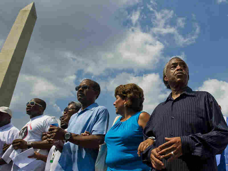 The Rev. Al Sharpton (right) walks with others past the Washington Monument