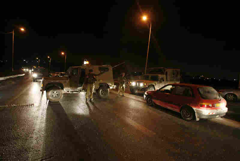 Israelli soldiers block a road near a shooting in the West Bank on Tuesday.