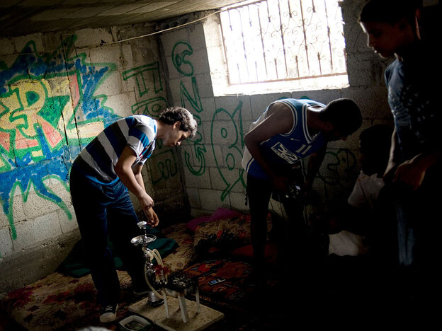 At a refugee camp in Gaza, Palestinian teenagers hang out in a graffiti-covered warehouse July 28. They give classes on the art of graffiti and break dancing.