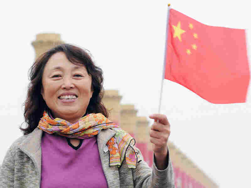 A smiling woman holds a Chinese flag