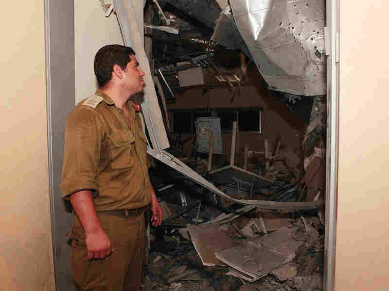 An Israeli military officer in Sderot examines the damage from Palestinian rocket fire