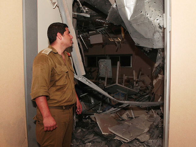 An Israeli military officer examines the damage after a rocket fired by Palestinian militants from Gaza hit a building near the southern Israeli town of Sderot on July 31.