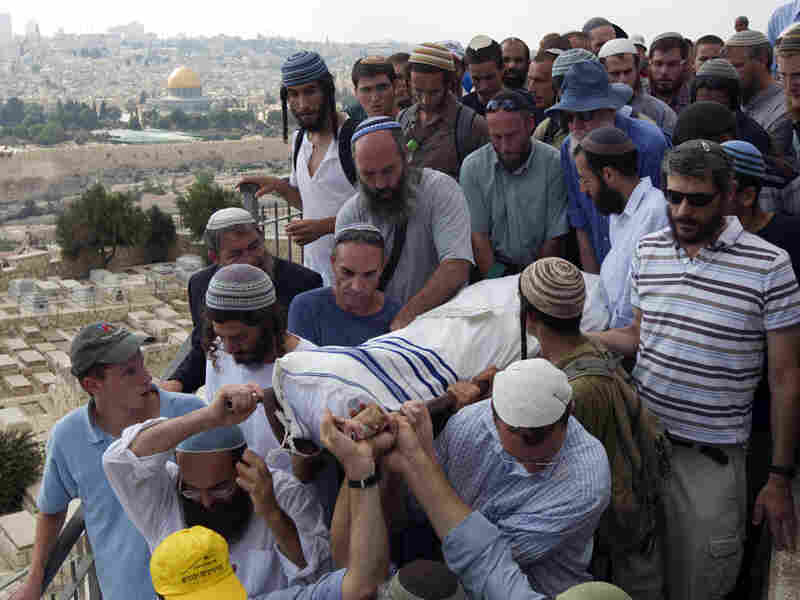 Israeli settlers carry bodies to burial