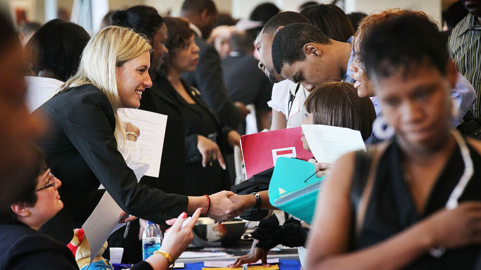 Job seekers speak with recruiters during a career fair sponsored at Malcolm X College in Chicago this summer.