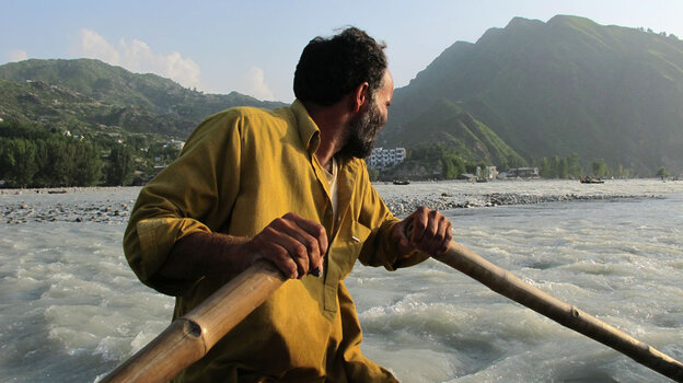 An oarsman navigates his inner-tube boat across the raging Swat River