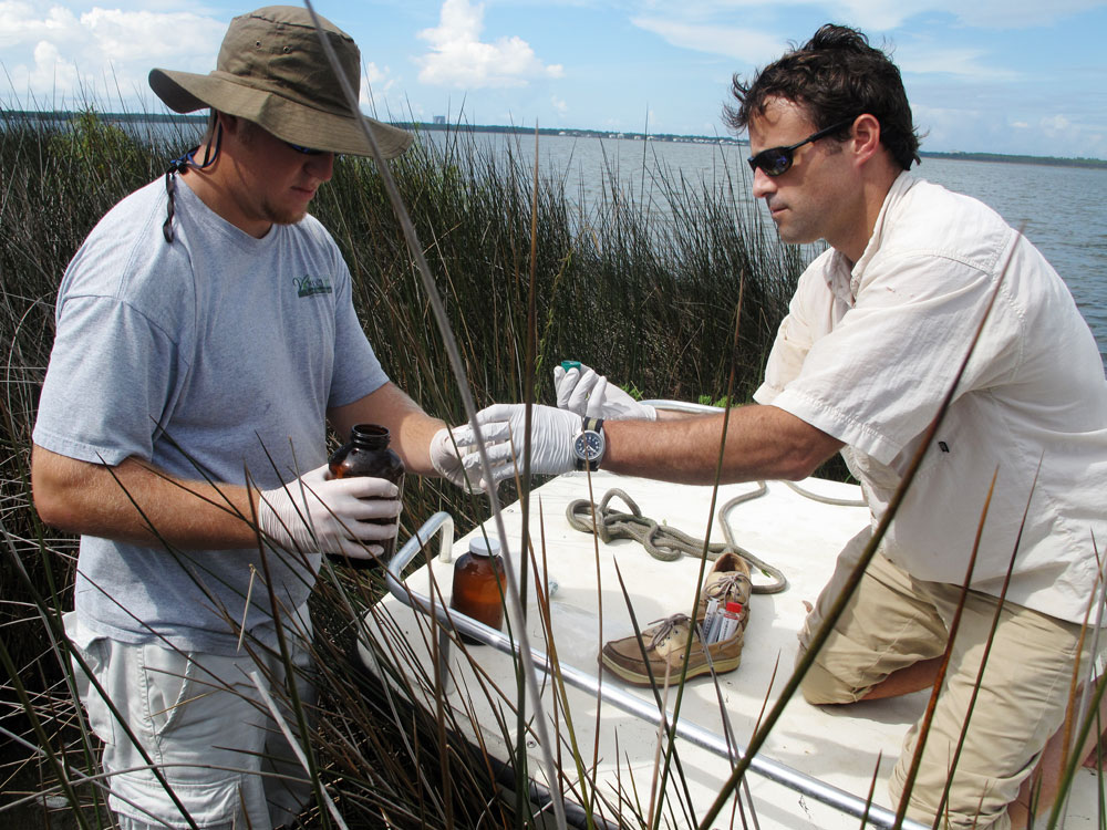 Geologist Mark White gives Jody Blount a bottle to collect a water sample.