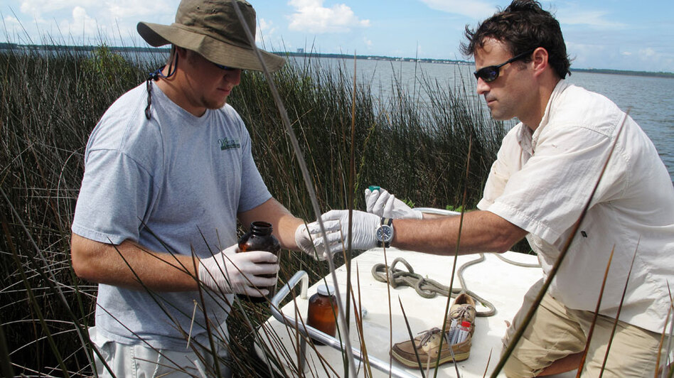 Geologist Mark White (right) of Cameron Consulting gives Jody Blount a bottle to collect a water sample. Weeks Bay is one of 15 sites selected for long-term monitoring for effects of the BP oil spill.
