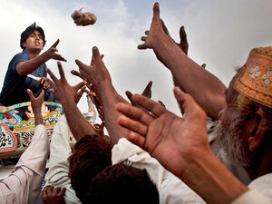 Pakistanis displaced by flooding reach for food aid thrown by a volunteer.