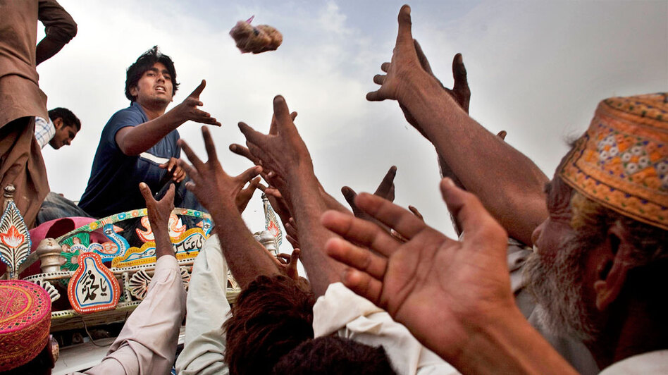 Pakistanis displaced by flooding reach for food aid thrown by a volunteer during a distribution outside a temporary camp operated by the Pakistan army in Sukkar, southern Pakistan.