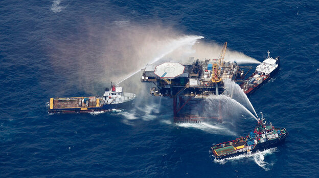 Boats spray water on an oil and gas platform that exploded in the Gulf of Mexico