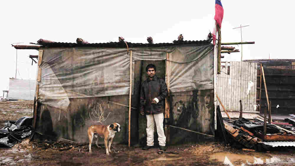 A man stands in front of a shack he built at a temporary camp Penco's port in Concepcion
