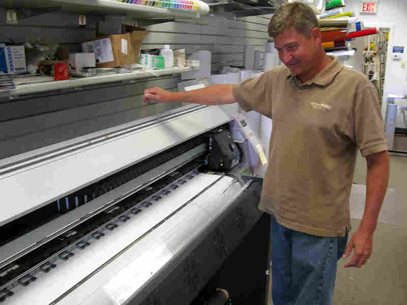 Chuck Eldridge stands over a printer in his Signarama franchise in Cherry Hill, N.J.