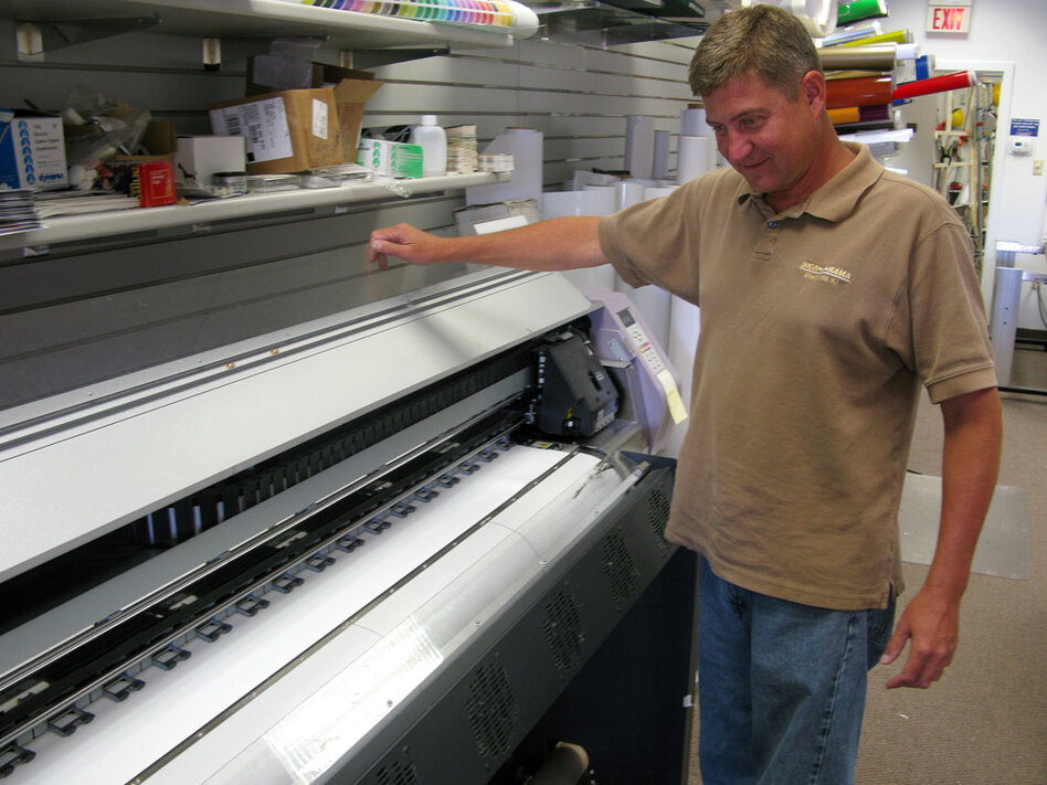 Chuck Eldridge stands over a printer in his Signarama franchise in Cherry Hill, N.J. He says technology has helped him do more work with the same number of people, so he doesn't need to hire new workers.