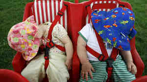 Two babies nap in their multiple-chil