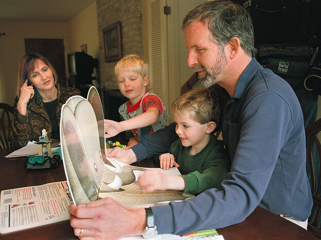 Jennifer May watches her sons Wyndham and Carson introduce children's storybooks to Mike May, after surgeries to correct blindness in one of Mike's eyes in 2000.