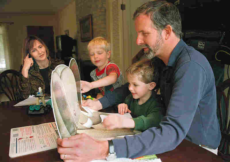 Jennifer May watches her sons Wyndham and Carson introduce children's storybooks to Mike May.