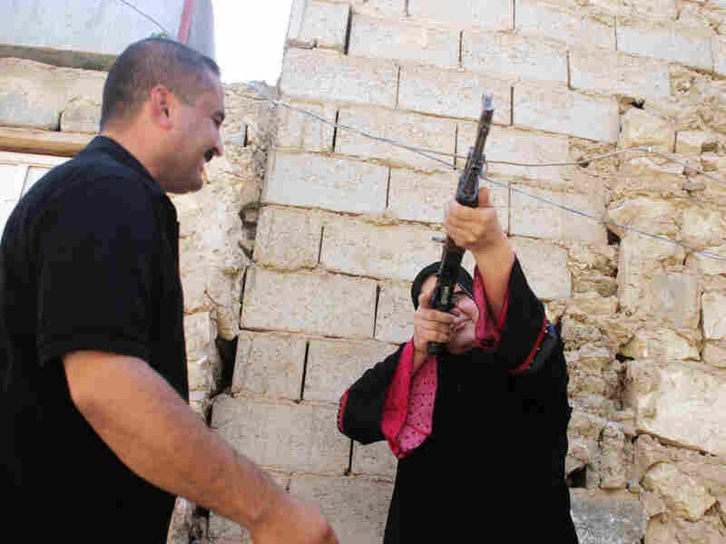 Ali Abu Jihan teaches his wife, Shaima Saadi, how to use an AK-47.