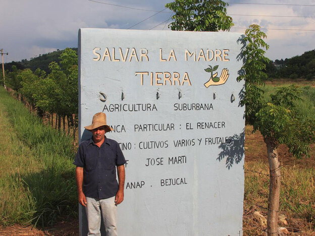 "Cuban farmer Lorenzo Ramos stands next to a sign that reads ""Save Mother Earth."" He hopes to open a market stand at the site, to sell his fruit directly to customers. He received a five-acre plot through a government plan to help the island grow more of its own food."