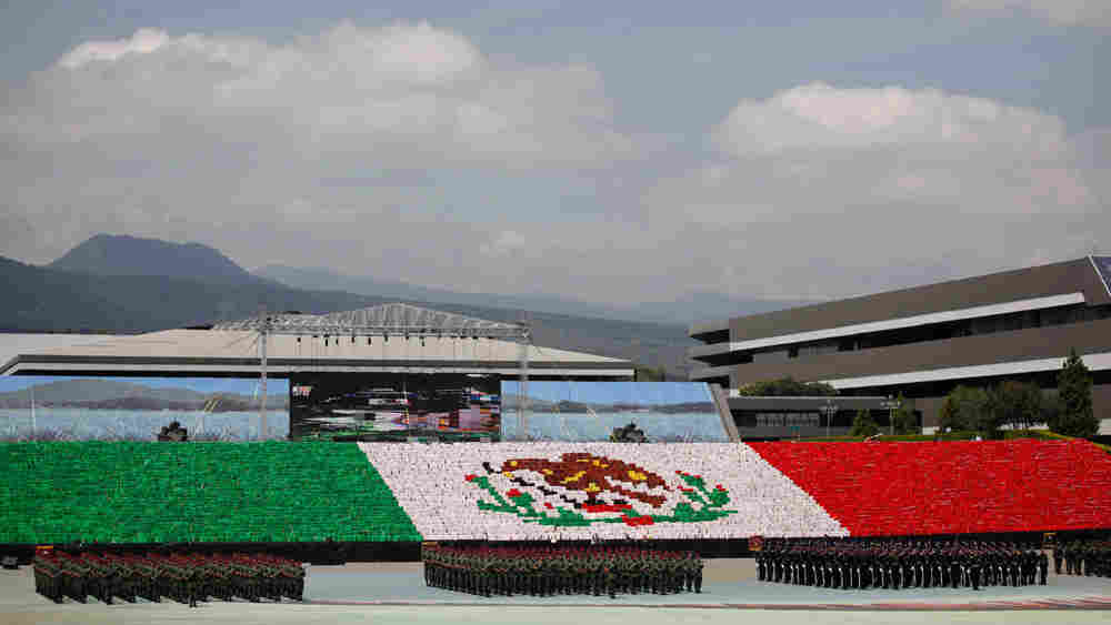 Soldiers line up in front of Mexico's flag during bicentennial celebrations in Mexico City