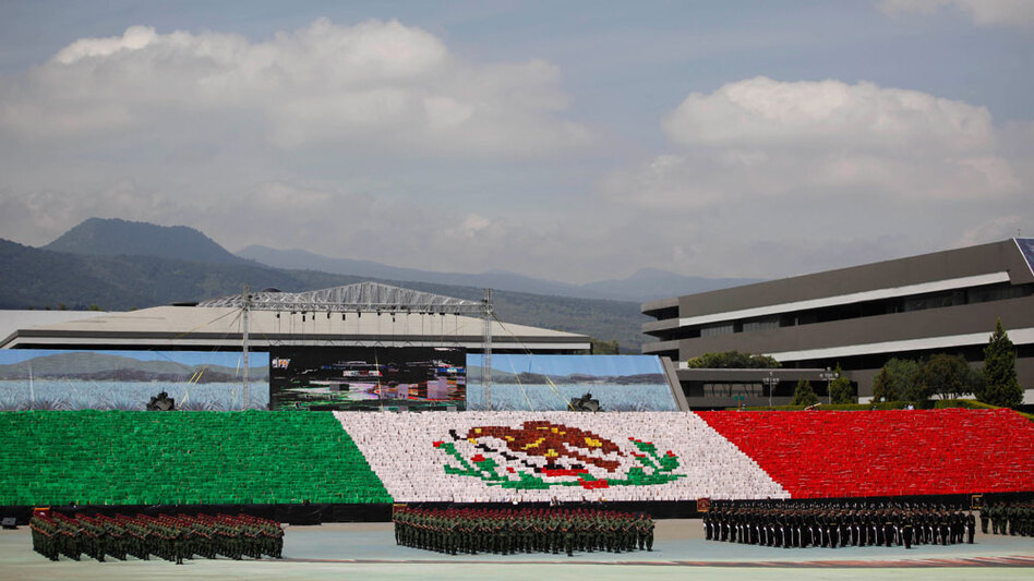 Soldiers line up in front of Mexico's flag Monday in preparation for bicentennial celebrations in Mexico City. Festivities surrounding the 200th anniversary of Mexico's 1810 independence uprising are being scaled back in some parts of the country due to security concerns amid the wave of drug-related violence.