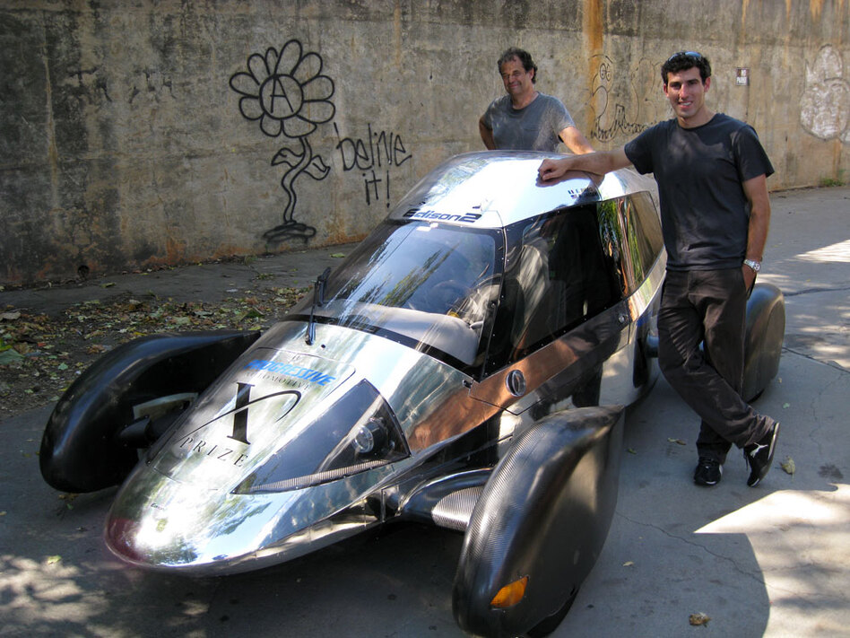 Team Edison2's Oliver Kuttner (left) and Brad Jaeger, one of the team's professional race car drivers, with the Very Light Car that won the mainstream class of the X Prize competition. (Joshua Brockman/NPR)