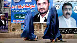Afghan women walk past campaign posters in Jalalabad, Afghanistan