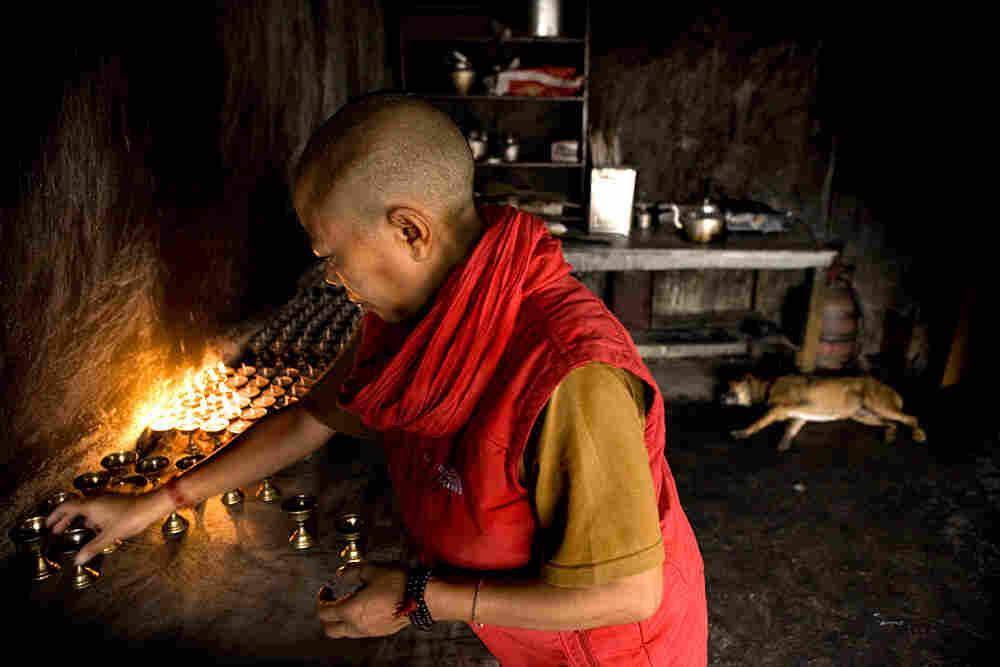A Tibetan nun lights candles