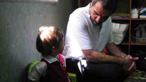 Mahmoud Jamal (right) sits with a student at Jerusalem Kindergarten.