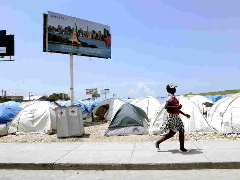 Billboards tower over tent camp near Haiti's international airport